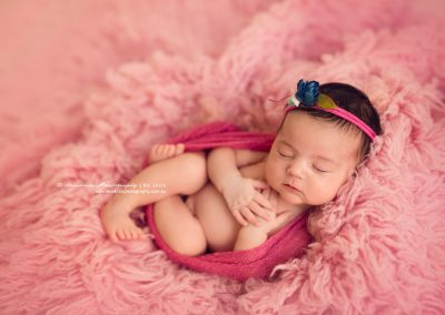 Beautiful-newborn-lying-on-pink-rug