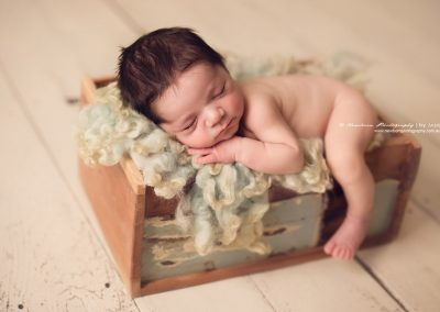beautiful-newborn-boy-sleeping-in-box-with-leg-hanging-down