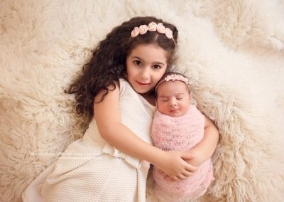 big-sister-holding-newborn-sister-in-her-arms