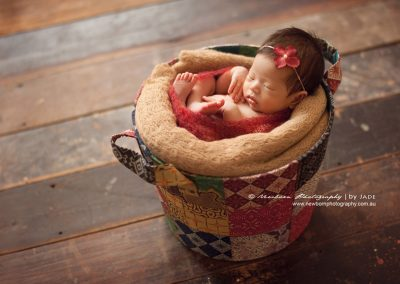 cute-asian-newborn-girl-in-colourful-fabric-basket